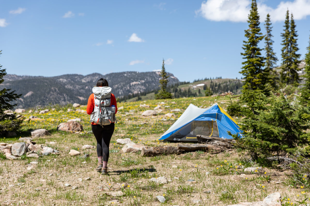 Women hiking up to tent